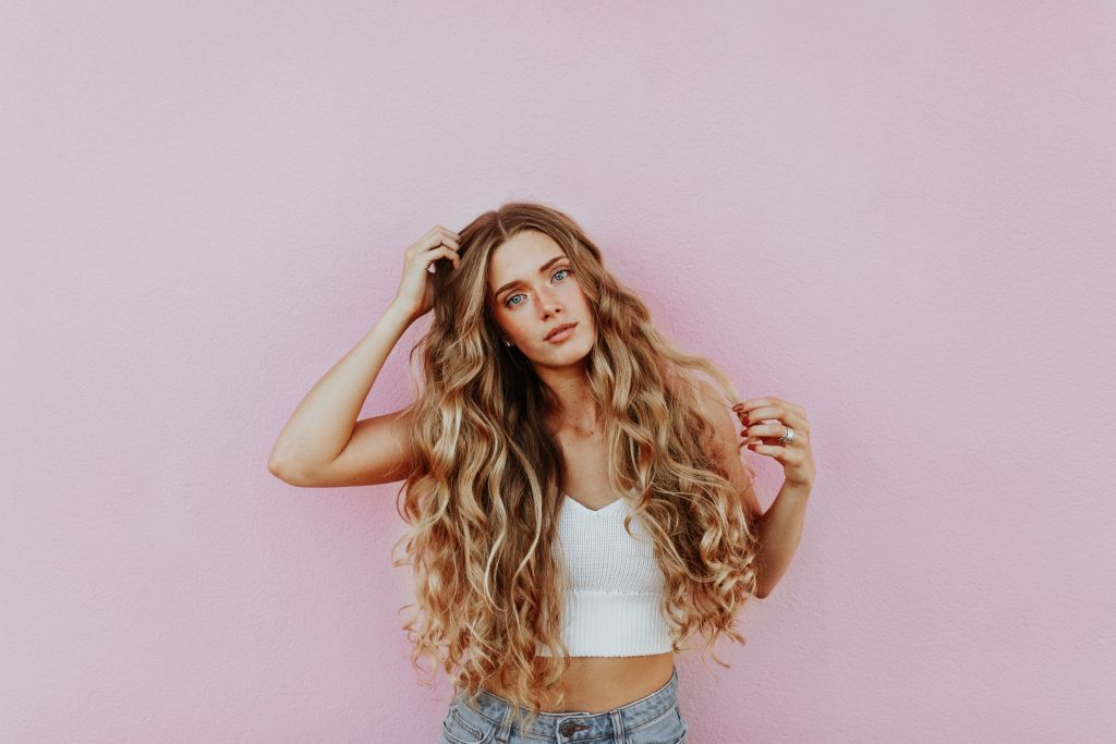 a curly girl in a pink background