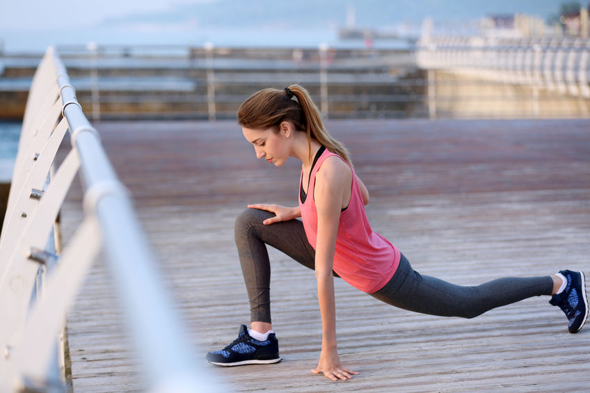 Young woman doing exercises on pier